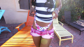 Ebony babe Misty Stone stripteasing near the pool